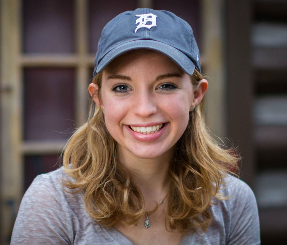 Photo of girl with short blonde hair smiling wearing a grey short sleeve shirt, a silver necklace, and a Detroit Tigers navy baseball cap