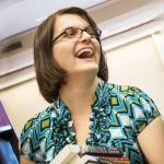 laughing woman with brown hair and glasses