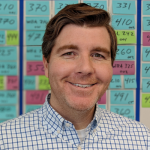 Image of Casey McArdle in front of post it notes.