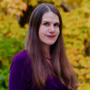 woman with long brown hair in purple shirt against yellow flower background