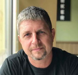 man with short hair and goatee looking into camera seriously
