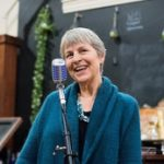 woman standing in front of microphone wearing blue sweater