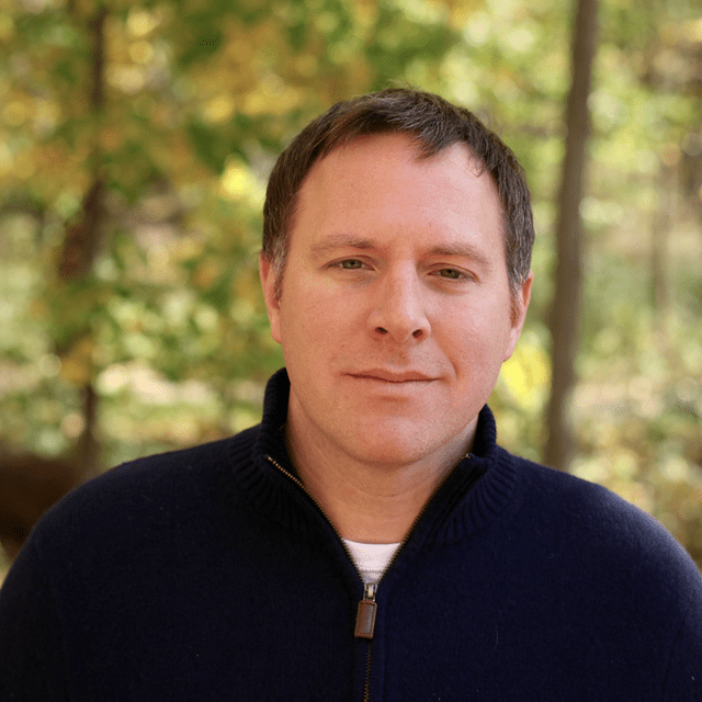 portrait of a man with brown hair wearing a blue zip up sweater