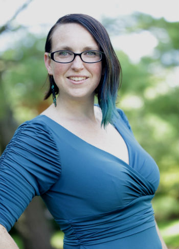 a women wearing glasses and a blue top with black and blue hair