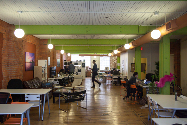 photo of an office setting with white tables and brick walls