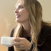 woman holding steaming cup of coffee and looking off left