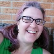 woman with glasses and dyed hair smiling brightly