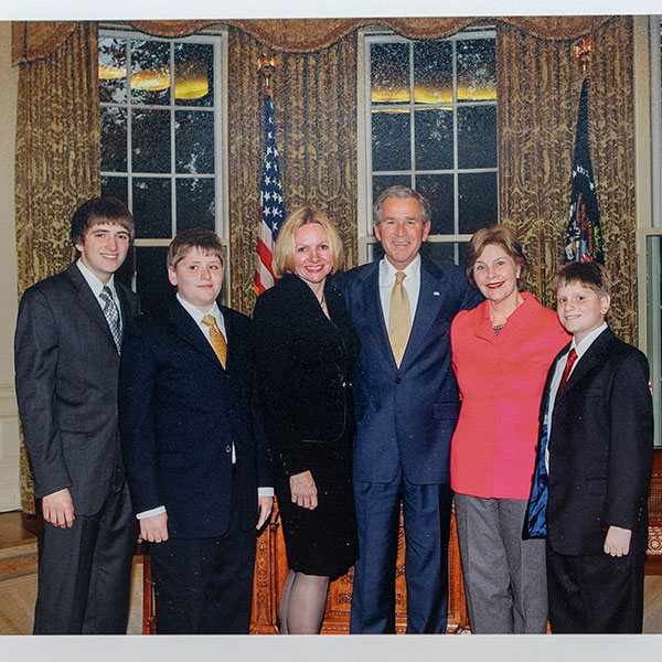 six people taking a picture dressed in suites at the White house