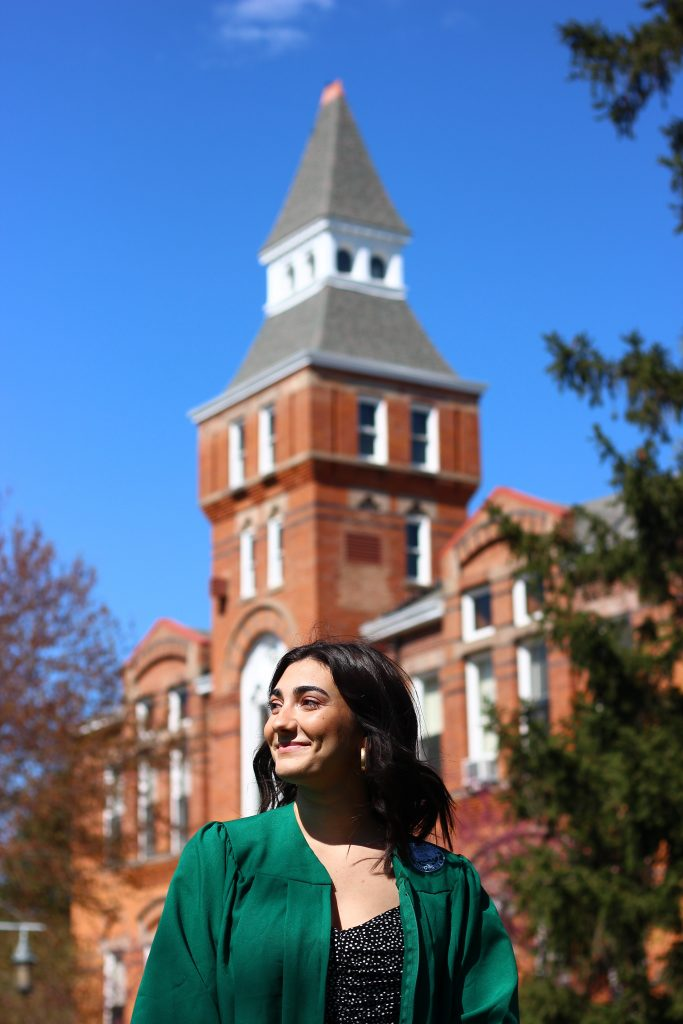 a girl standing in front of a brick building wearing a green gown