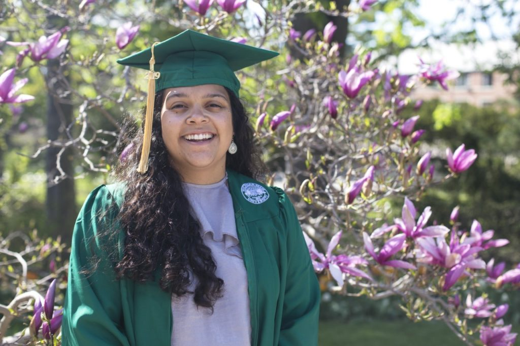 girl with long dark hair in green cap and gown