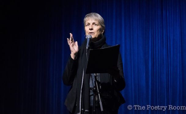 A woman with short gray hair wearing a black turtleneck sweater is standing and speaking into a microphone. Her hand is raised slightly. The curtain behind her is blue.