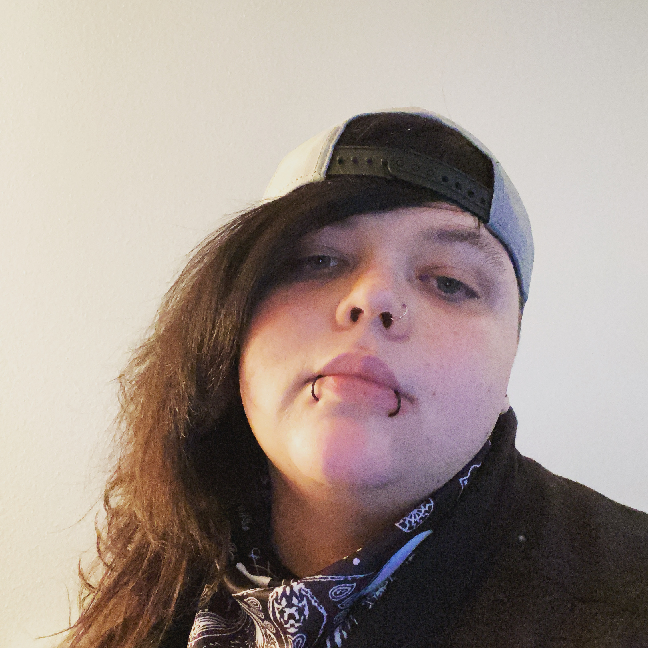 A person with lip piercings wearing a ball cap backwards