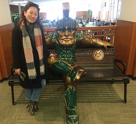 student with sparty statue