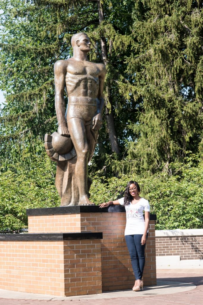 Ja'La Wourman standing next to the statue of Sparty on MSU's campus