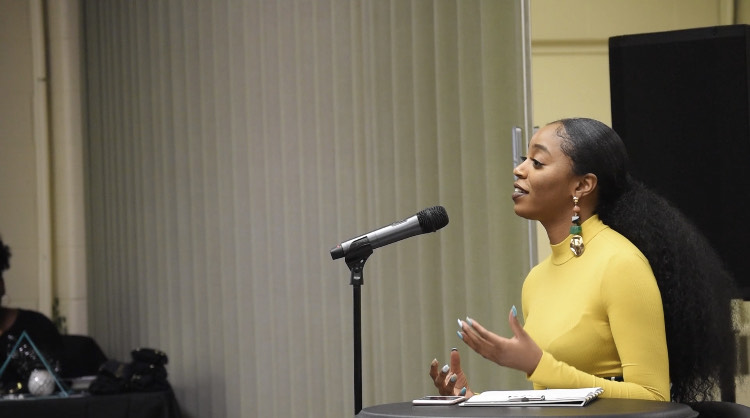 Ja'La Wourman speaking at a podium