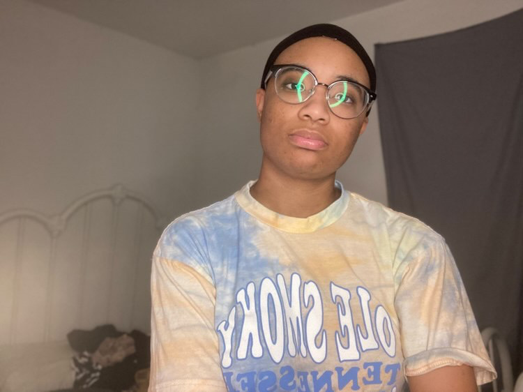 A young Black person wearing glasses and a tee shirt