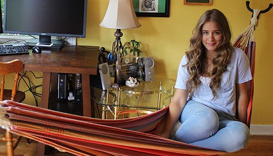 Emily Wilson chilling in her hammock in her home office