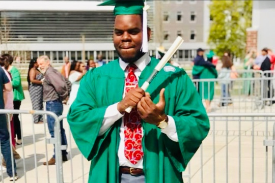 a man in a green cap and gown with a red tie holding a diploma