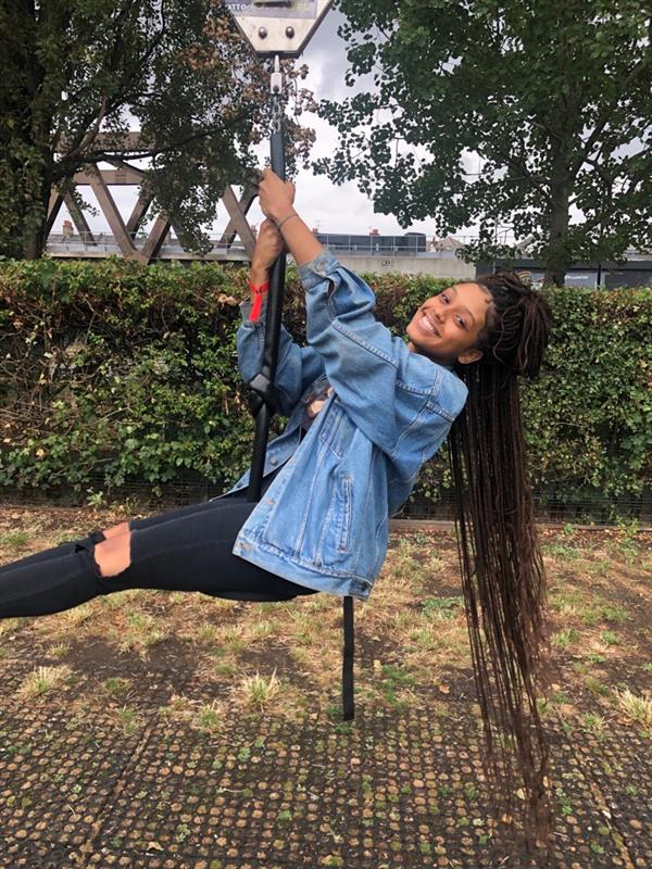 image of a girl with long braided hair swinging wearing a jean jacket and black jeans