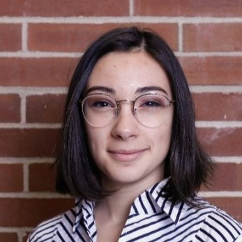 Headshot of a person with shoulder-length brown hair and glasses.
