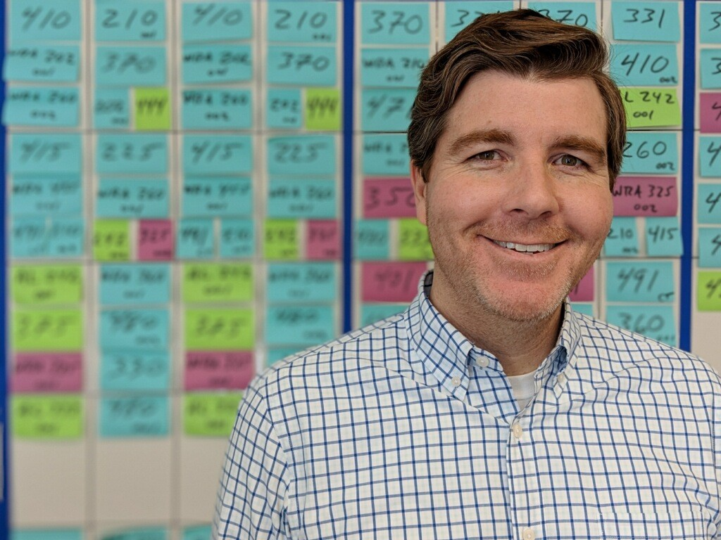 Man with reddish-brown hair is smiling. Behind him are blue, green, and pink sticky notes with numbers on them.