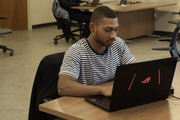 An African-American student typing on a laptop